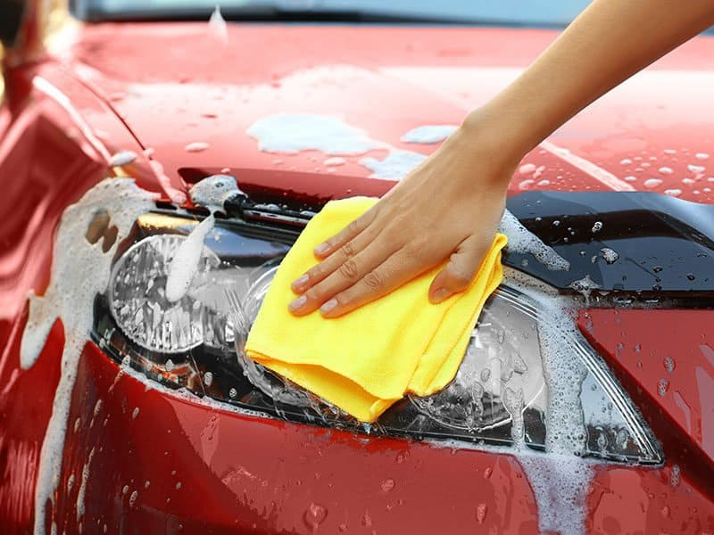 Servicewoman Washing Car